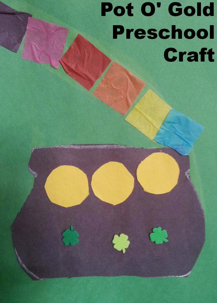 Pot of gold craft that is made with construction paper. The black pot has 3 giant gold coins, 3 shamrocks on it, and tissue paper make the rainbow and has violet, pink, red, orange, yellow, and blue.